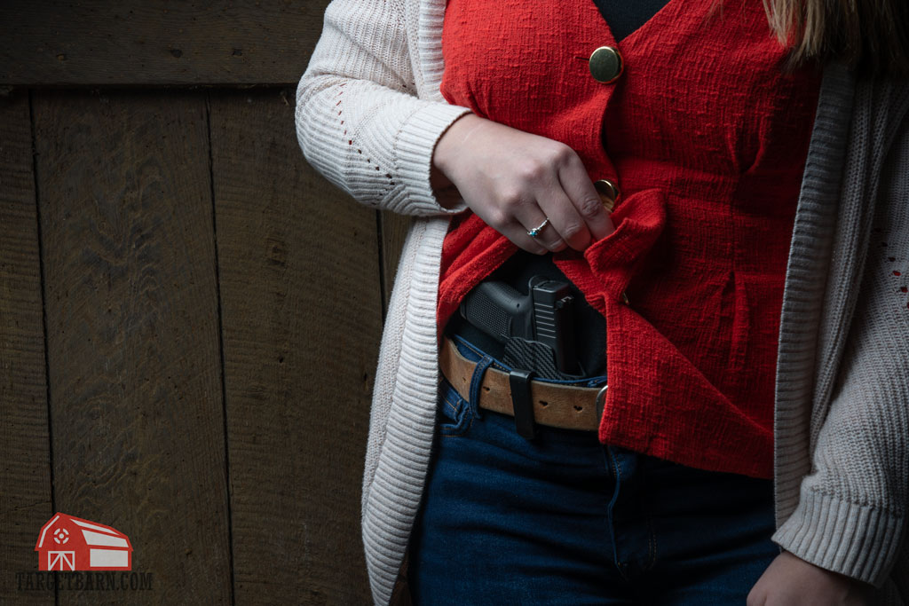 a woman conceal carrying a single stack glock pistol