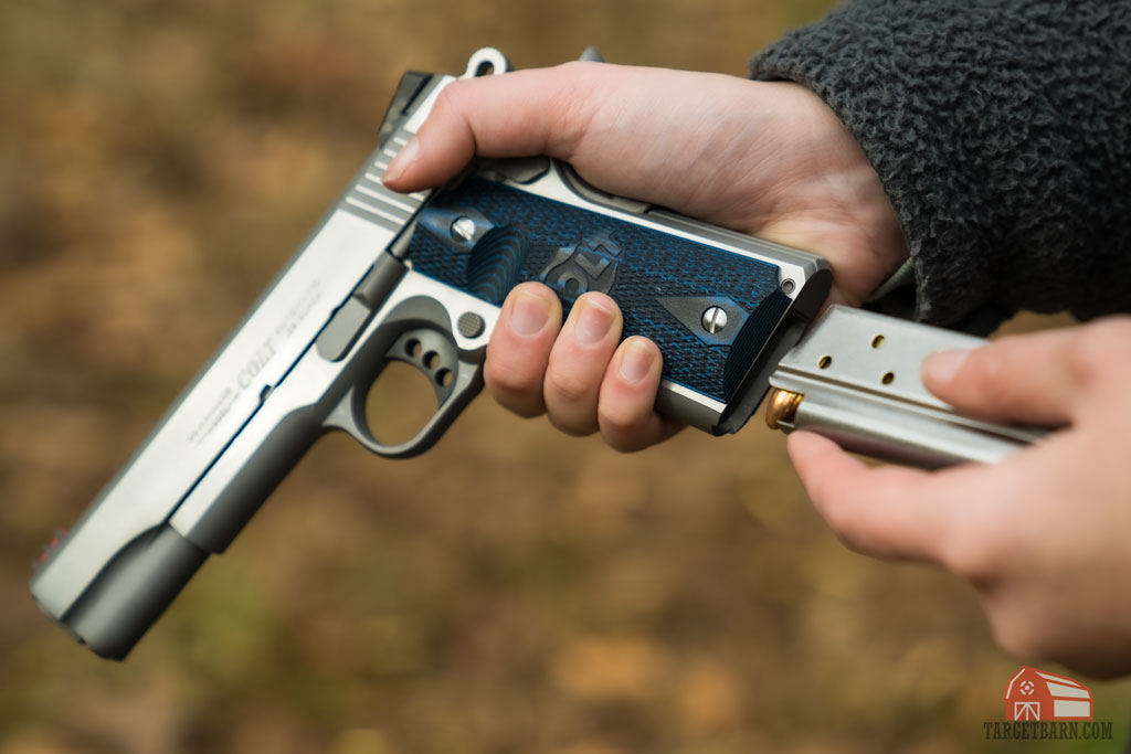 a modern colt .38 super 1911 competition gun being loaded