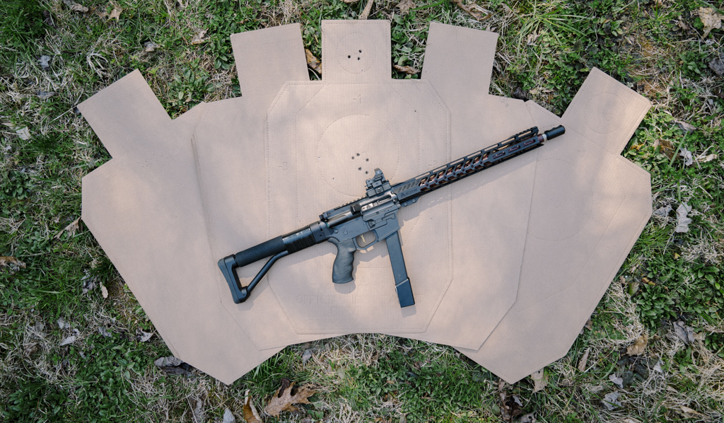 a pistol caliber carbine laying on top of idpa targets