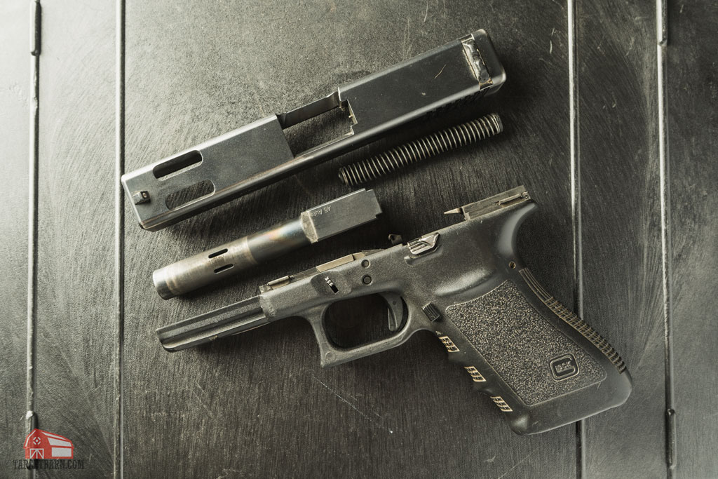 a disassembled glock 21c with a ported barrel