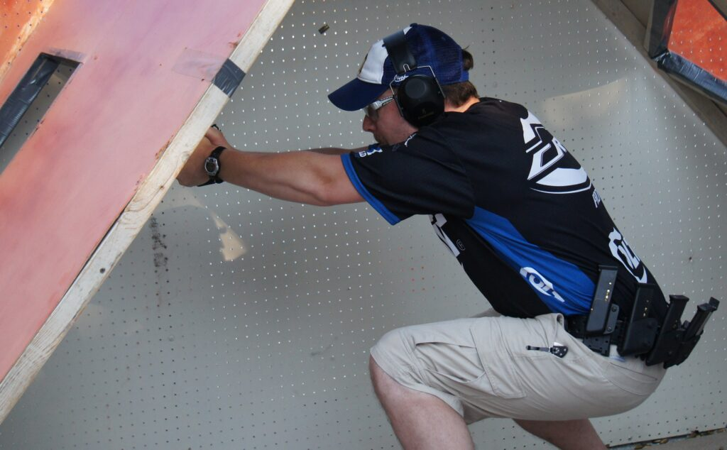 Caleb crouched down shooting at a USPSA match