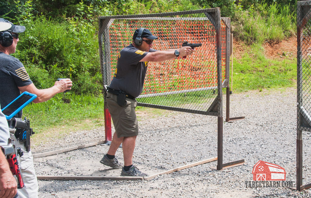 a uspsa competitor shooting a stage in carry optics division