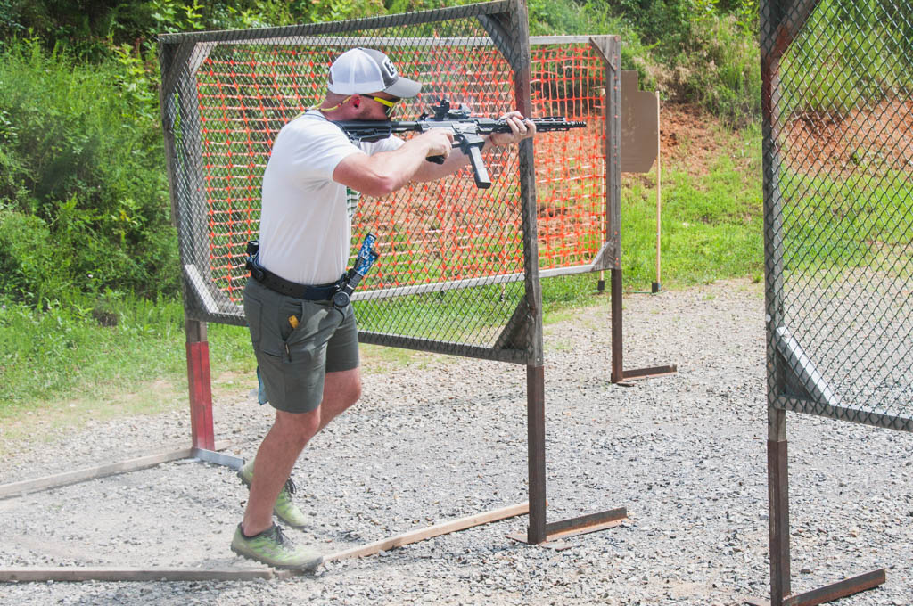a PCC shooter at a USPSA match using a second off-set red dot optic for a sharp corner
