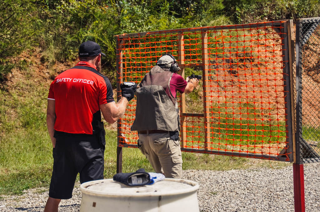an idpa range officer watching a shooter