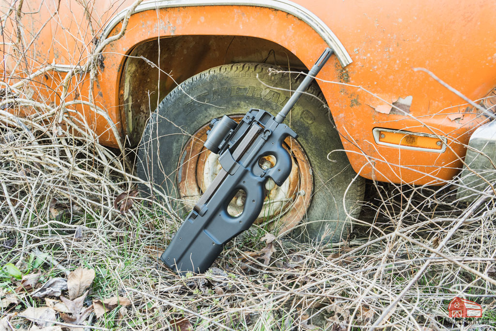 an fn ps90 with optic leaning against and old orange truck
