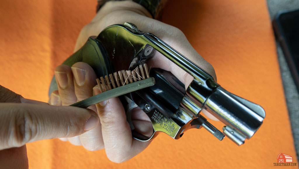 using the bronze brush to clean the face of the frame of a revolver