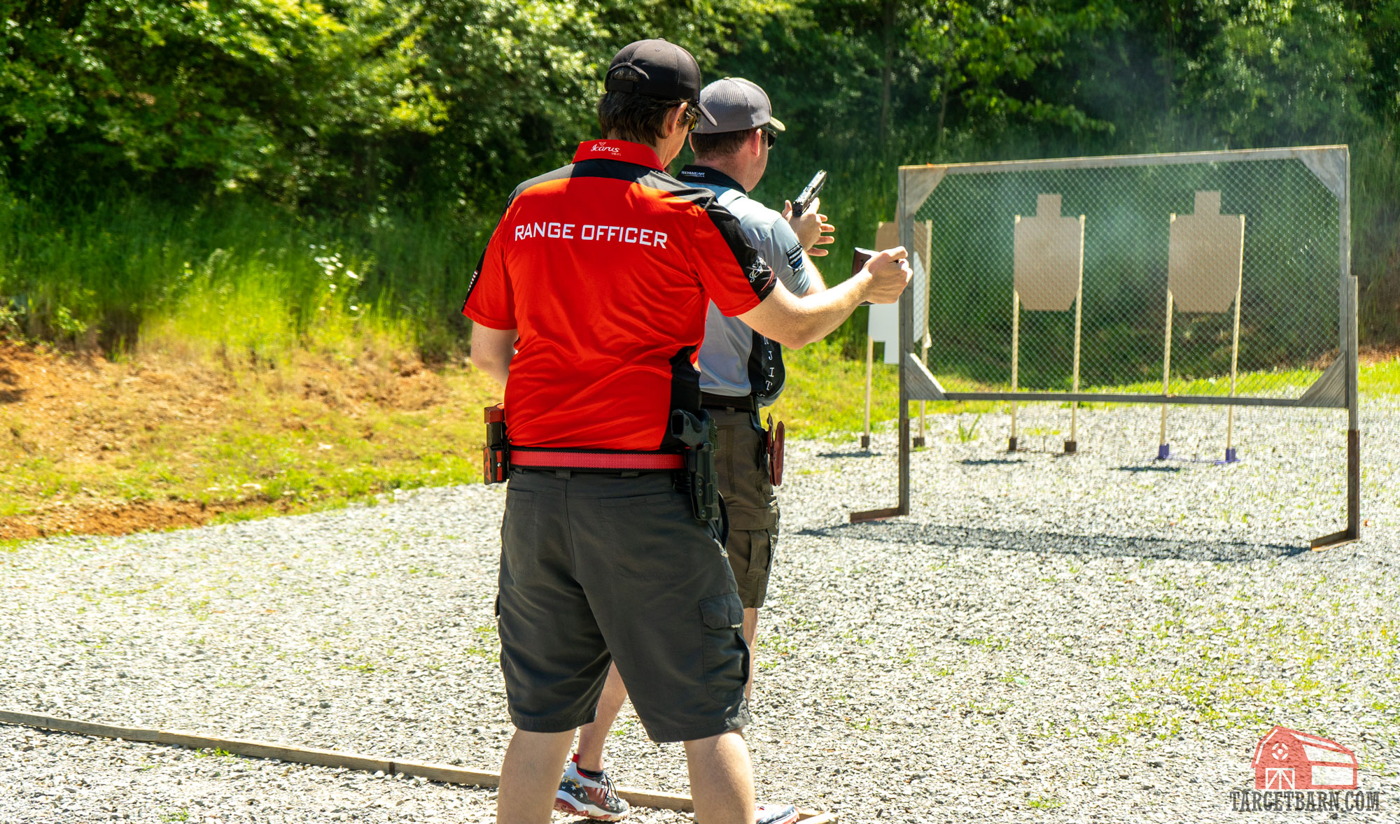 a range officer timing a shooter during a stage at a uspsa match