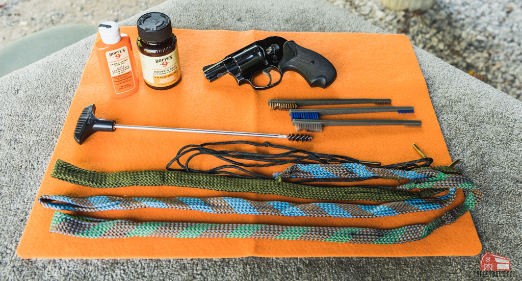 a revolver and cleaning supplies on a cleaning mat