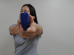 Pistol held with head turned to one side