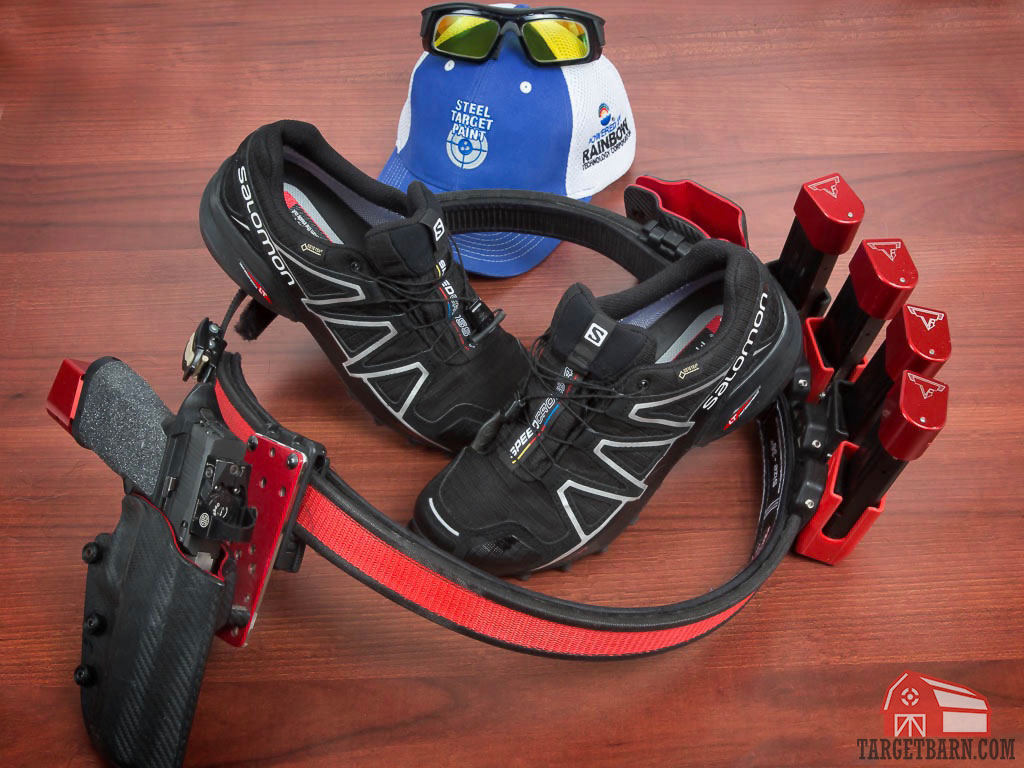 a competition gun and belt, salomon shoes, a hat, and protective eyewear displayed to demonstrate gear needed for a uspsa match